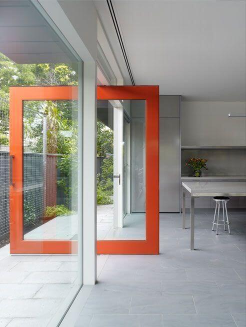 Porta pivotante de vidro com borda laranja Foto de Joel Eriksson