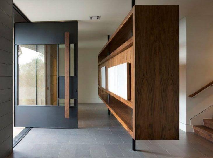 Porta pivotante preta com puxador grande de madeira Foto de Jon Luce