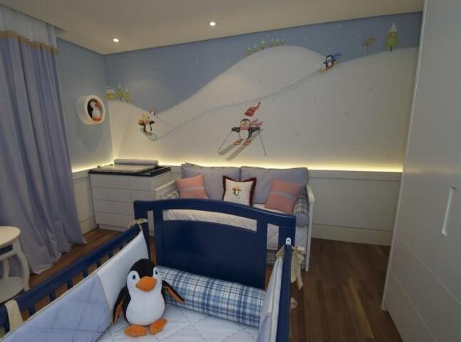 Quarto de bebê menino com berço azul e parede com desenhos de pinguins Projeto de Lucia Tacla