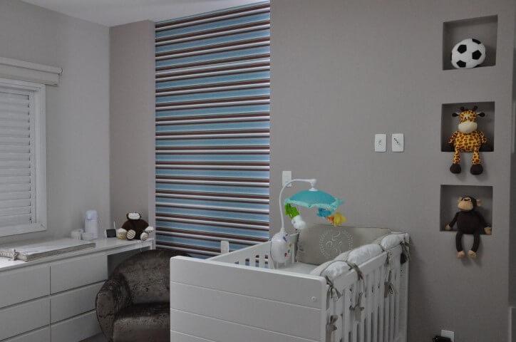 Quarto de bebê menino com parede cinza e papel de parede listrado Projeto de Claudia Breias