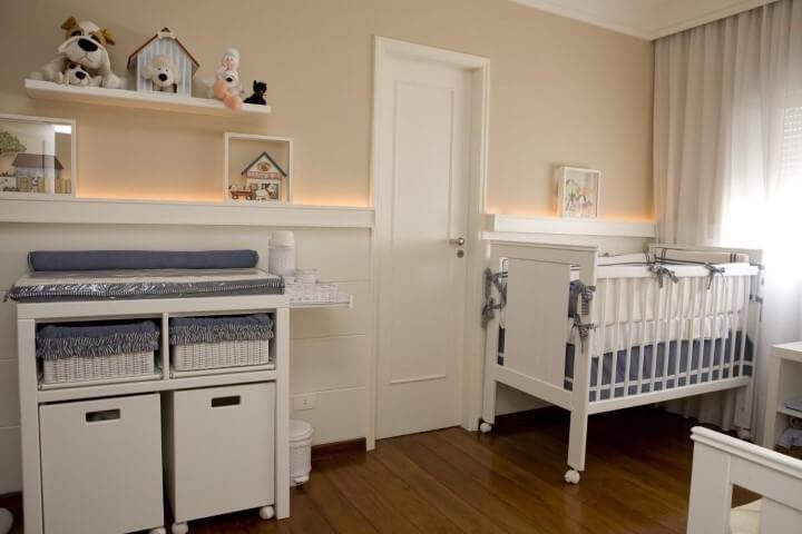 Quarto de bebê menino com paredes bege e móveis claros com detalhes azuis Foto de Lucia Tacla
