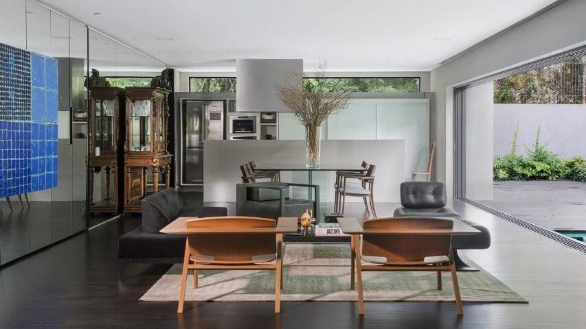 Sala com móveis de madeira cadeiras e cristaleira Projeto de Jayme Bernardo