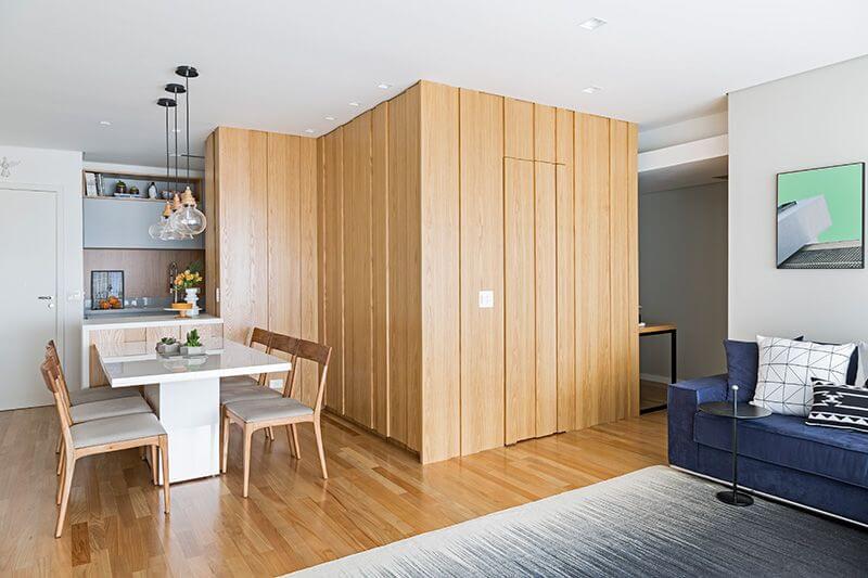 Sala com móveis de madeira paredes e cadeiras Projeto de Doob Arquitetura