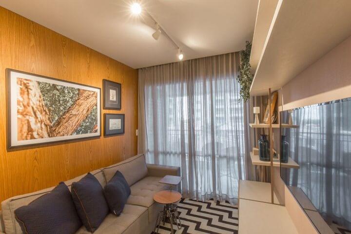 Sala de TV com móveis de madeira e painel na parede Projeto de Emerson Vasconcelos