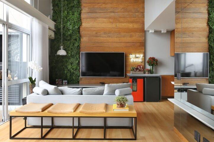 Sala de TV com móveis de madeira painel rústico na parede alta Projeto de Estudio AE