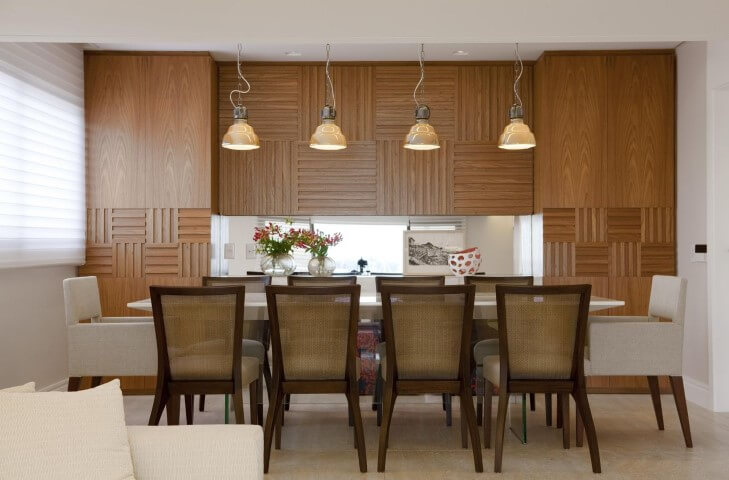 Sala de jantar com móveis de madeira e painel na parede Projeto de Marcelo Rosset