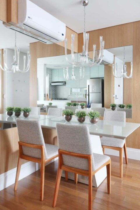 Sala de jantar com móveis de madeira painel na parede e cadeiras Projeto de Danyela Correa