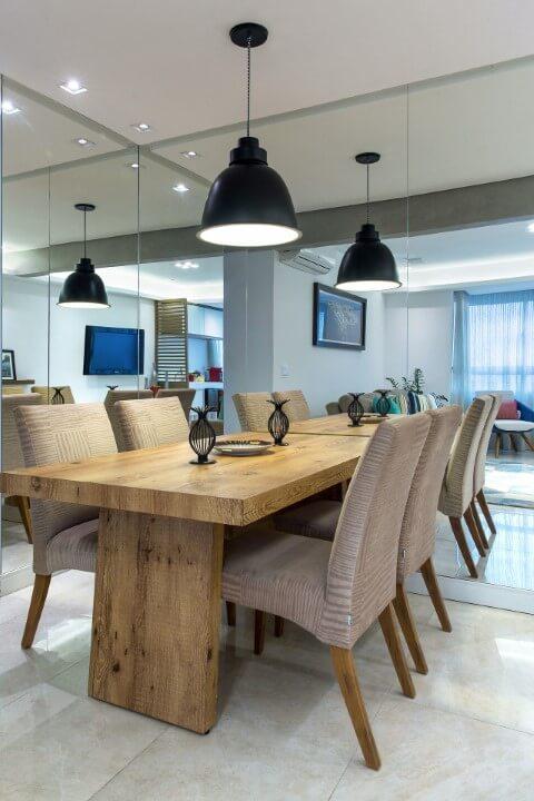 Sala de jantar espelhada com móveis de madeira mesa e pés de cadeira Projeto de Milla Holtz