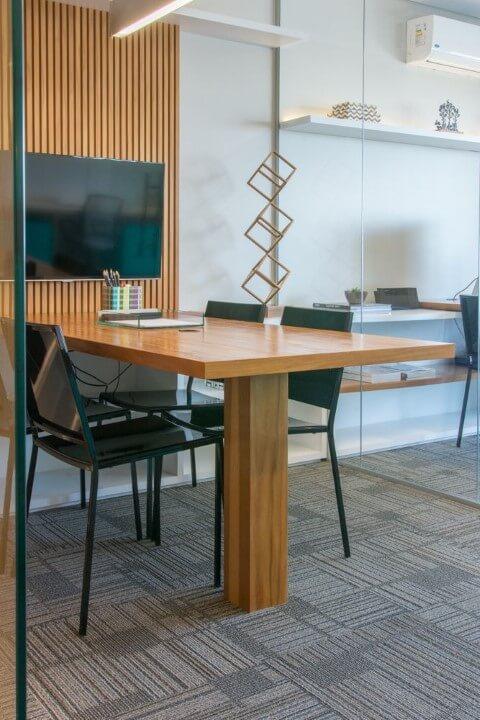 Sala de reunião com móveis de madeira mesa embutida no painel Projeto de Danyela Correa
