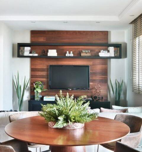 Sala integrada com móveis de madeira mesa redonda e painel de TV Projeto de Tetriz Arquitetura
