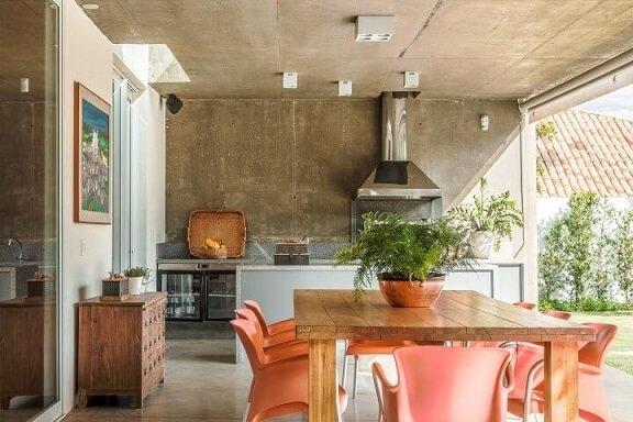 Varanda gourmet com móveis de madeira mesa com cadeiras laranja Projeto de AMC Arquitetura