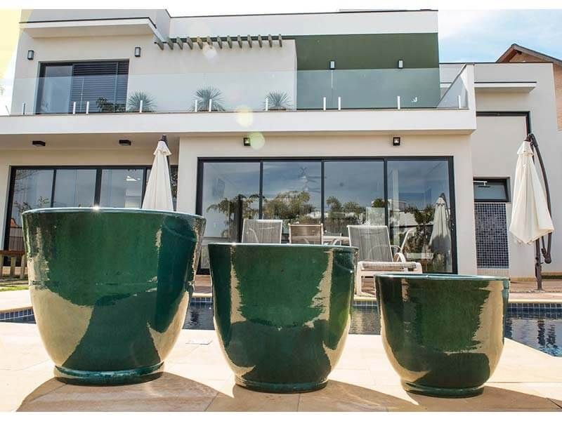 Vasos de cerâmica verdes na área externa da casa Foto de Terra Asia