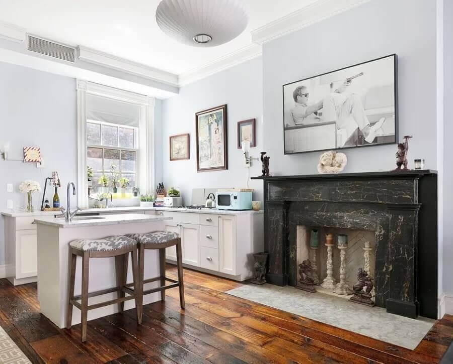 decoração casa emma stone com piso de madeira e revestimento em mármore preto para lareira