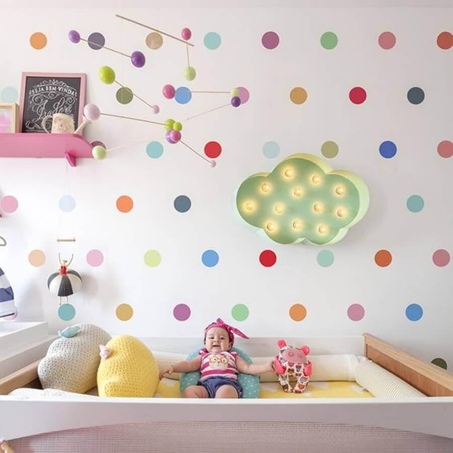 decoração colorida com papel de parede de bolinhas e enfeites para quarto de bebê com mobile colorido sobre o berço Foto Pinterest