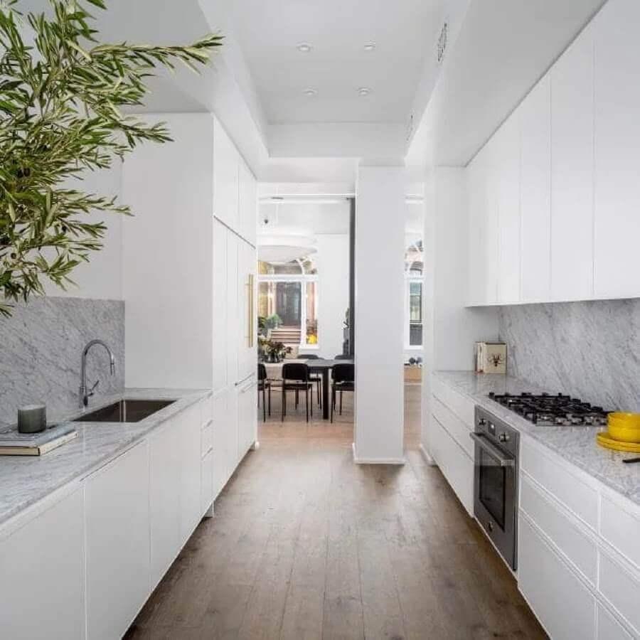 decoração cozinha Emily Blunt toda branca com armários planejados e piso de madeira