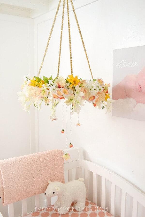 decoração delicada com enfeites para quarto de bebê feminino com arranjo de flores no mobile sobre o berço Foto Pinosy