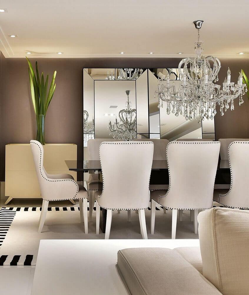 decoração elegante com lustre pendente para sala de jantar com espelho apoiado na parede e tapete preto e branco Foto Tetriz Arquitetura e Interiores