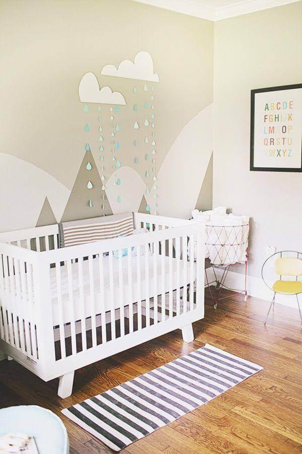 decoração em tons neutros com enfeites para quarto de bebê com berço branco e adesivos de montanhas na parede Foto Noaki Jewelry
