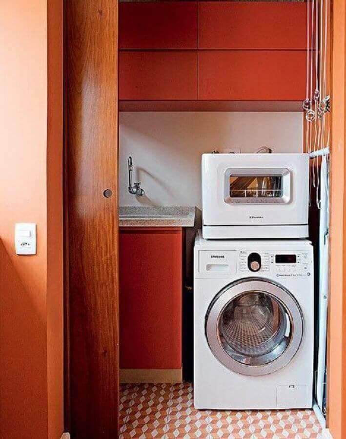 decoração lavanderia pequena com armários planejados e porta de correr de madeira Foto Novolar Empreendimentos