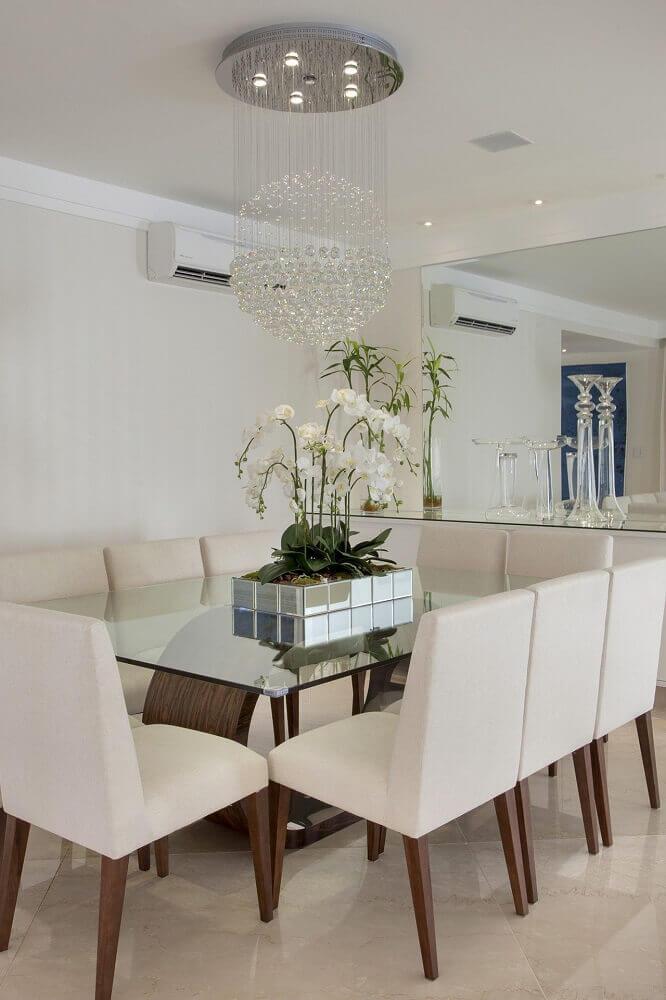 pendente de cristal para sala de jantar sofisticada decorada com mesa de vidro e parede espelhada Foto Aaron Guides