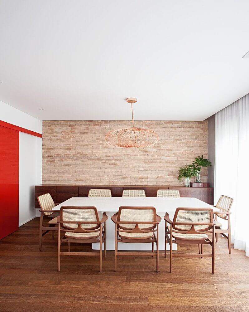 pendente moderno para sala de jantar decorada com parede de tijolinho e cadeiras de sisal Foto Korman Arquitetos