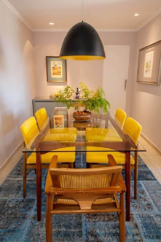 pendente sala de jantar pequena decorada com tapete azul cadeiras amarelas e mesa de vidro Foto Apê Vinte Dois