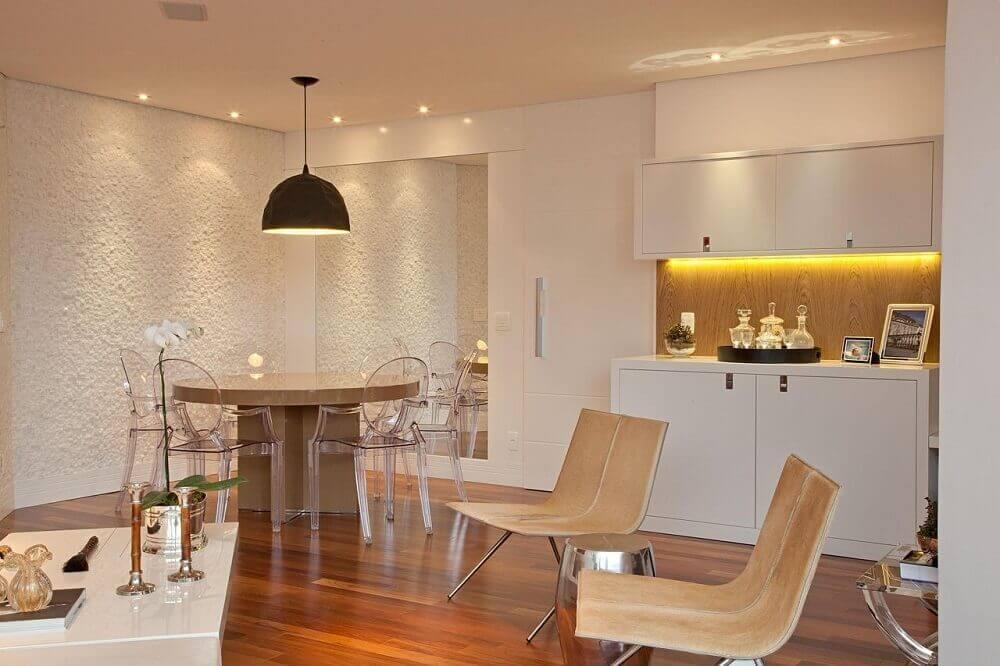 pendente sala de jantar pequena decorada em tons neutros com cadeiras de acrílico transparente Foto Patricia Kolanian Pasquini