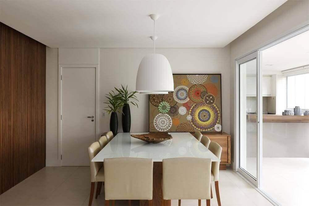 pendentes para sala de jantar decorada em tons neutros com buffet de madeira e quadro apoiado na parede Foto Cíntia Mara Petronetto
