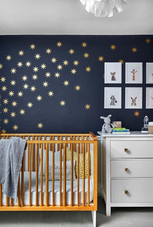 quadros para quarto de bebê com parede azul escura decorada com estrelas douradas e berço de madeira Foto Pinterest