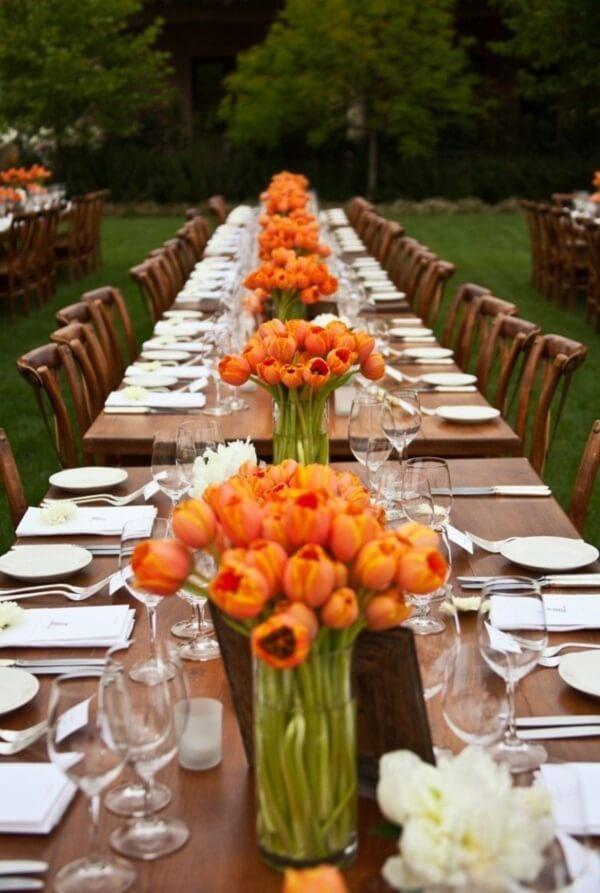 A mesa de madeira fica ainda mais linda com arranjo de tulipa