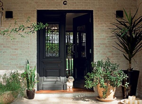 A porta de entrada preta se contrasta com a parede de tijolinho. Fonte: Pinterest