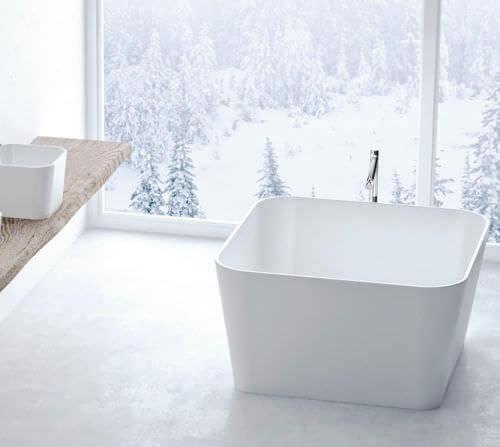 Banheira pequena branca em banheiro com bancada de madeira Foto de Archi Expo