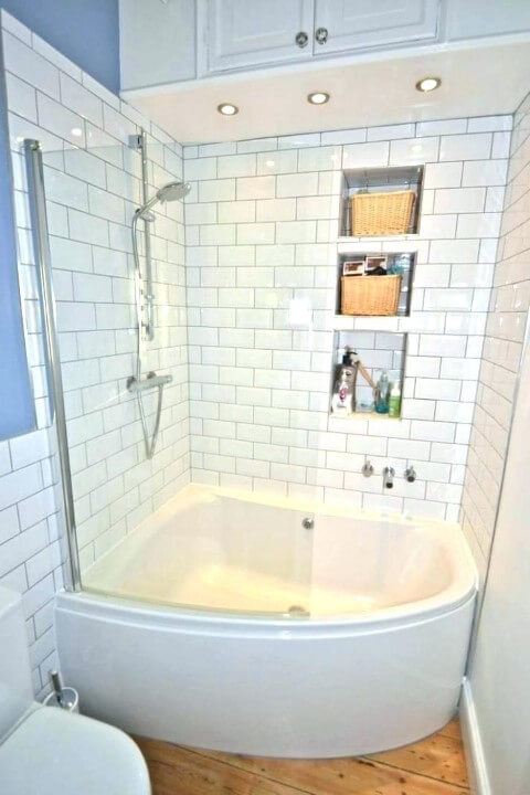 Banheira pequena de canto em banheiro com nichos embutidos na parede Foto de Buzzpipo