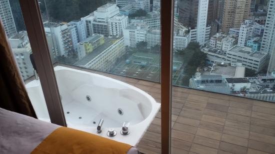 Banheira pequena em varanda de hotel com vista para cidade Foto de Cell Code