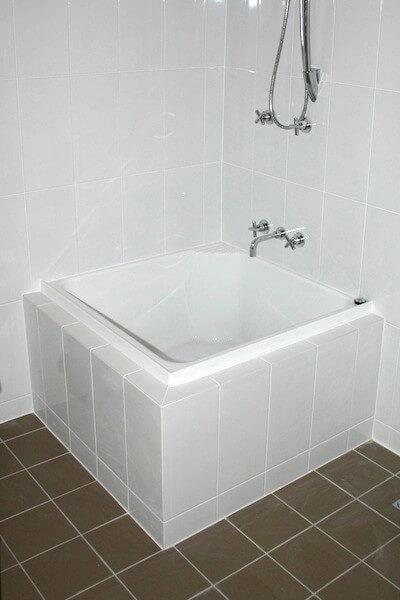 Banheira pequena quadrada em canto Foto de Prominade