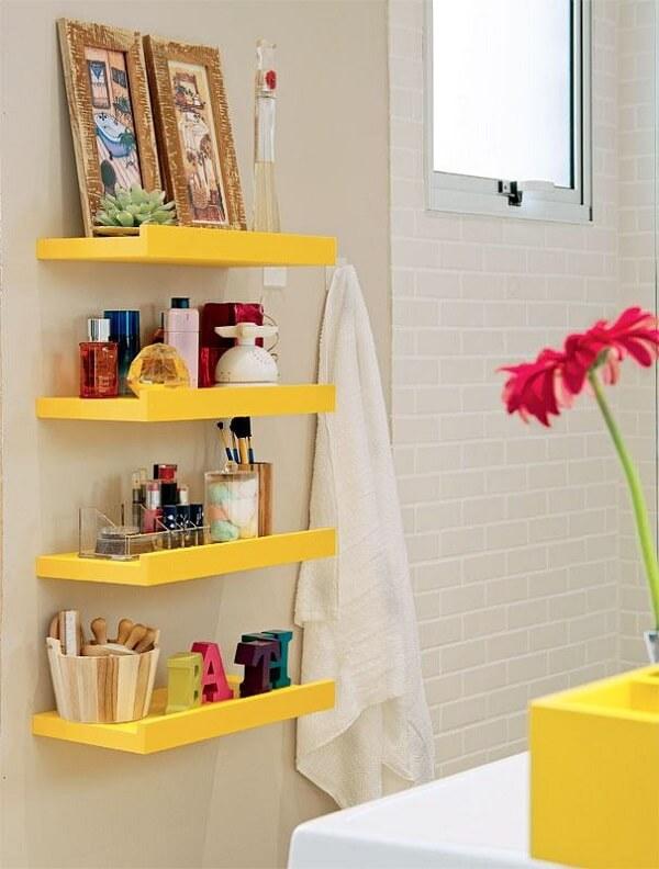 Banheiro pequeno decorado com prateleiras amarelas