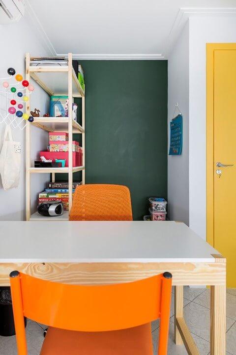 Consultorio com parede de chalkboard verde e cadeiras laranjas Projeto de Juliana Conforto