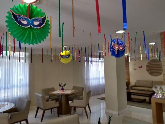 Decoração de carnaval com máscaras coloridas no teto Foto de AnaDê Festas & Lembranças
