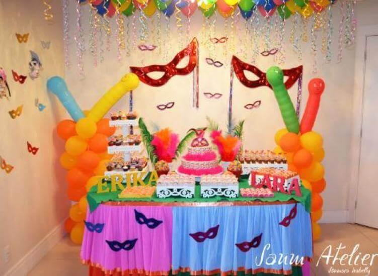 Decoração de carnaval com máscaras na parede e na mesa de doces Foto de Saum Atelier