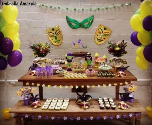 Decoração de carnaval com mesa de madeira e comidinhas Foto de Umbrella Amarela