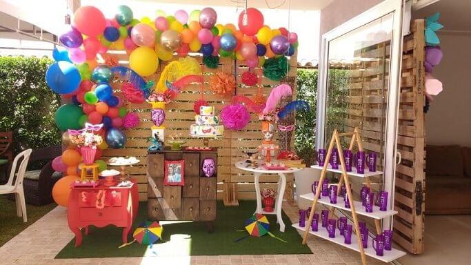 Decoração de carnaval com painel de madeira com balões coloridos Foto de Parceria Fest