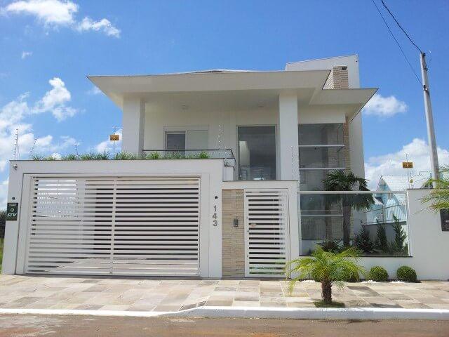 Fachada de casa moderna com muro de vidro e portão branco combinando com a porta Foto de Marcos Biazus