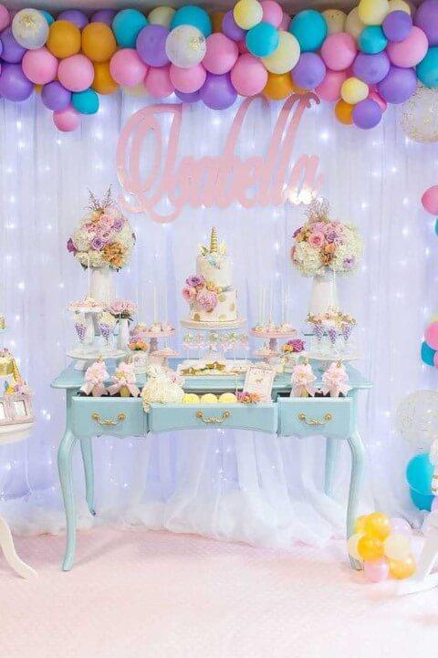 Festa de unicórnio com balões coloridos e mesa do bolo em tons pastel Foto de Brad Pike