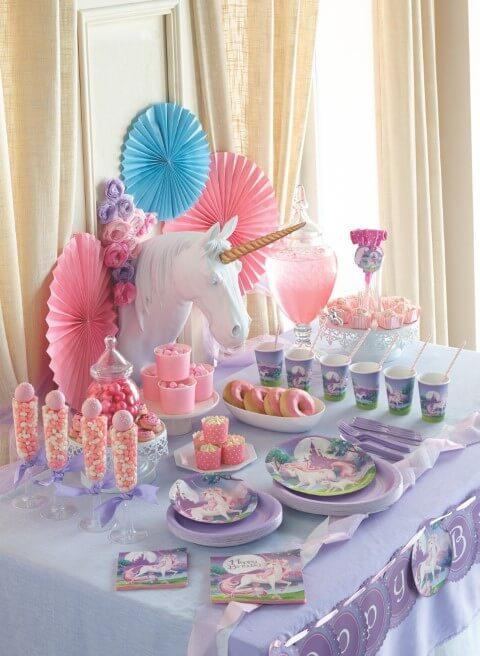 Festa de unicórnio com escultura de cabeça de unicórnio na mesa dos docinhos Foto de Sweety