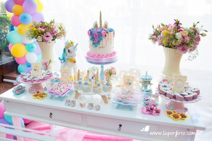 Festa de unicórnio com mesa bem decorada de bolo Foto de Lu Porfírio