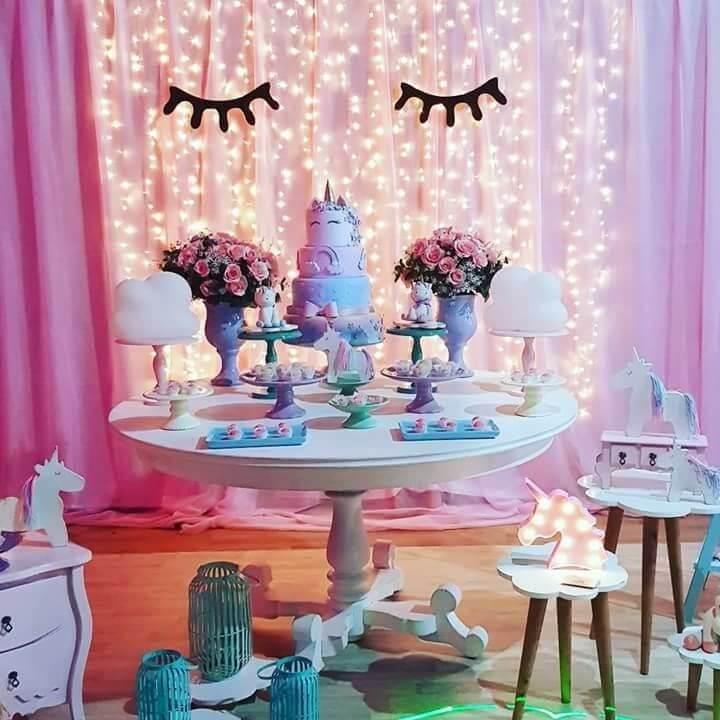 Festa de unicórnio com mesa de bolo pequena e painel com luzes pisca pisca Foto de Cell Code