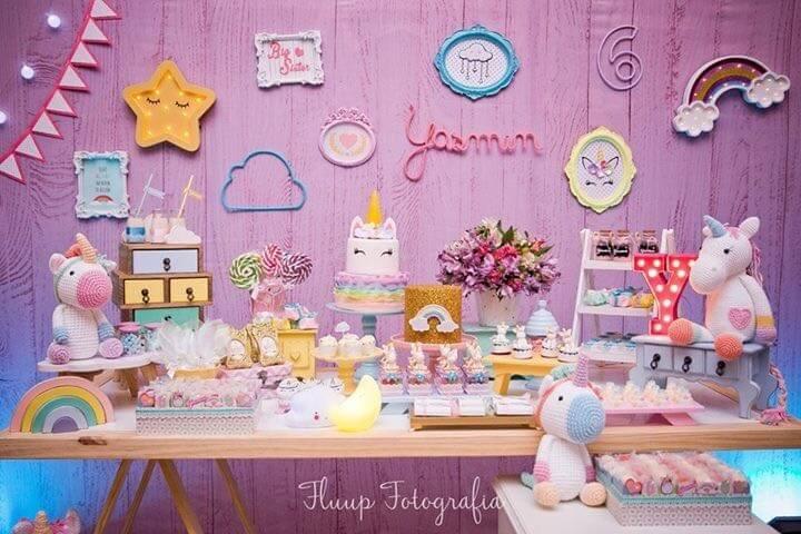 Festa de unicórnio com mesa do bolo com bichos de pelúcia e parede colorida Foto de Fluup Fotografia