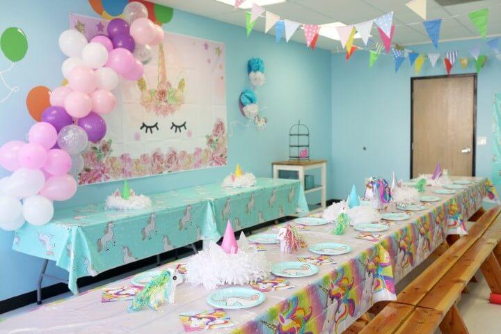 Festa de unicórnio com mesa do bolo e dos convidados com decoração combinando Foto de Imagine Play Elk Grove