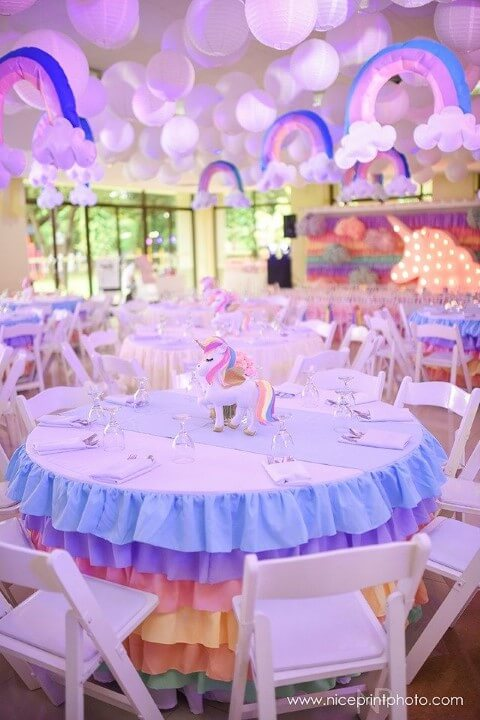 Festa de unicórnio com mesas decoradas e arco-íris no teto Foto de Nice Print Photo