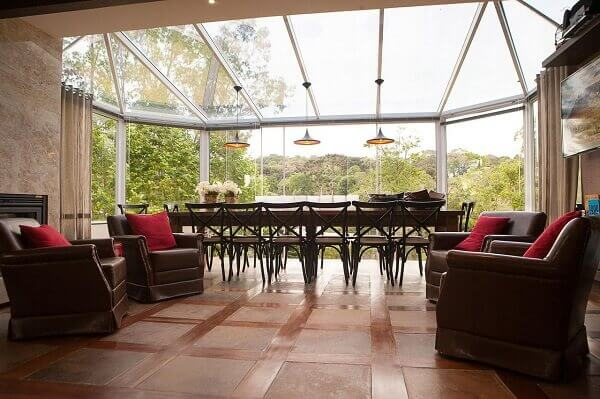 Marrom em poltronas de varanda com almofadas vermelhas
